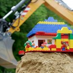 Kita Neubau: Baggerarm mit Duplo auf Sandhaufen